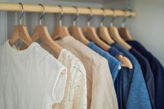 Roupa em ganchos no inclinação do armário de branco à obscuridade - azul foto de stock royalty free