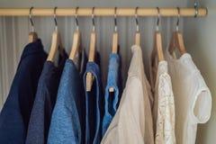 Roupa em ganchos no inclinação do armário de branco à obscuridade - azul foto de stock