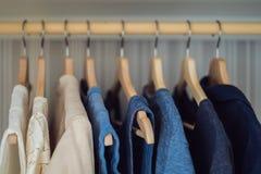 Roupa em ganchos no inclinação do armário de branco à obscuridade - azul fotografia de stock royalty free
