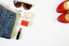 A roupa fêmea coloca horizontalmente com cosméticos e acessórios no fundo branco fotos de stock