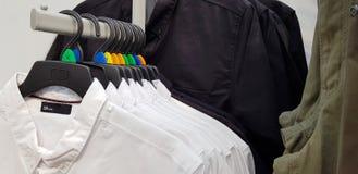 Roupa moderna em uma loja em um gancho Camisas e camisetas do dif imagem de stock