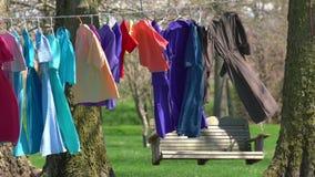 Roupa na linha que seca fora perto dos vestidos das mulheres coloridas do banco do balan?o vídeos de arquivo