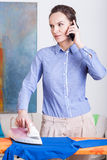 Roupa passando da mulher e fala no telefone celular foto de stock
