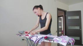 Roupa passando da mulher usando o ferro na tábua de passar a ferro após a lavanderia em casa filme