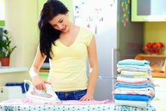 Roupa passando de sorriso da mulher em casa Imagem de Stock