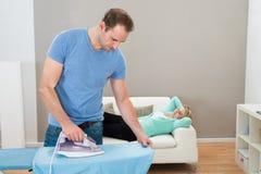 Roupa passando do homem quando mulher no sofá Fotografia de Stock Royalty Free