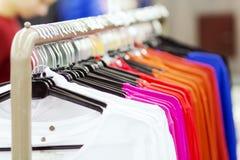 A roupa pendura em seguido em ganchos em uma loja da forma Coisas à moda em um boutique na moda Roupa de compra Conceito da compr Imagens de Stock