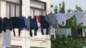 A roupa pesa e seca em uma corda em uma construção do Multi-andar em um bairro pobre da cidade vídeos de arquivo