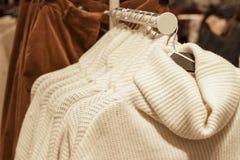 Roupa que pendura em ganchos na loja, escolha da roupa concentrada imagens de stock