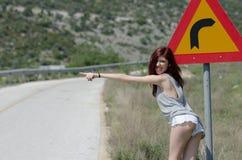 A roupa quente do roupa de senhora esconde uma volta do perigo do sinal de tráfego fotos de stock royalty free