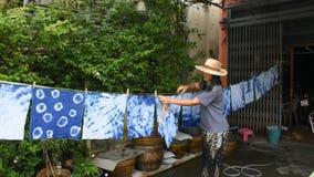 Roupa seca de suspensão de tingidura do processo da cor do índigo do batik tailandês do laço das mulheres no sol vídeos de arquivo