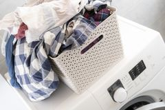 A roupa suja na cesta plástica em uma lavanderia coloca no mashine e na tabela de lavagem b imagens de stock royalty free