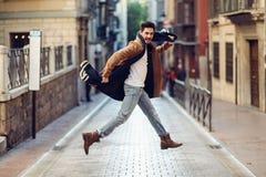 Roupa vestindo de salto do inverno do homem feliz novo no fundo urbano foto de stock royalty free