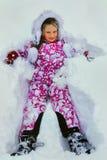 Roupa vestindo do inverno da menina que encontra-se na neve fotos de stock