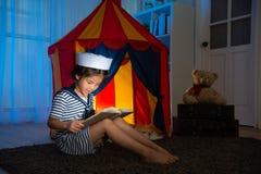 Roupa vestindo do marinheiro da menina que joga o jogo Imagem de Stock