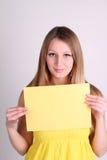 Roupa vestindo do yelow da menina e mostrar o cartão vazio Imagem de Stock Royalty Free