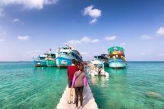 Roupen av turisten som skriver in till fartyg och går tillbaka därefter, till ön Royaltyfria Foton