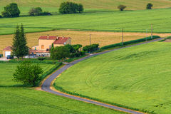 ROUSSILLON, FRANCE - MAY 2015: Winding road among green meadows Stock Photos
