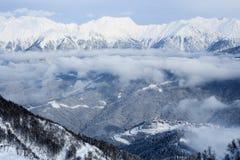 Route à skier hôtels de tourisme et hautes montagnes couverts de neige et de nuages à Sotchi Photographie stock libre de droits