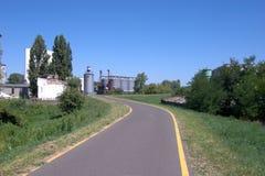 Route étroite avec des silos de grain au fond Images libres de droits