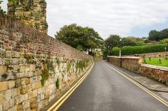 Route étroite droite garnie des murs en pierre Images stock