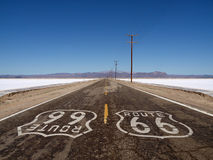 Route 66 Mojave Desert Salt Flats. Route 66 sign painted on rough Mojave desert salt flat highway pavement Royalty Free Stock Photos