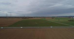 Route aérienne de contenu de bourdon de vue d'oiseau avec le trafic léger sur la ville extérieure et les terres arables clips vidéos