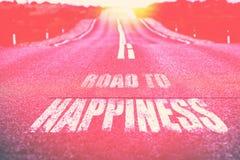 Route au bonheur écrit sur la route images stock