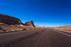Route avec des roches de côté gauche, désert de Death Valley photographie stock libre de droits