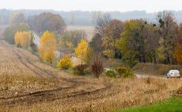 Route avec des voitures entre les arbres d'automne et les champs moissonnés Horizontal brumeux d'automne photo stock