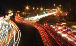 Route avec la circulation de véhicule la nuit avec les lumières troubles Photo libre de droits
