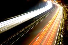 Route avec la circulation de véhicule la nuit avec les lumières troubles Photo stock