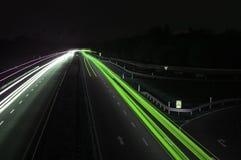 Route avec la circulation de véhicule la nuit avec les lumières troubles Photographie stock