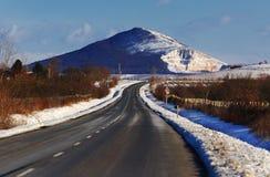 Route avec la montagne en hiver Photographie stock libre de droits