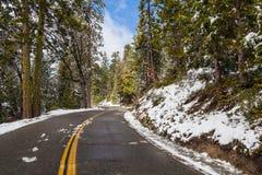 Route avec la neige et le ciel bleu Photographie stock libre de droits