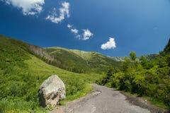 Route avec la roche dans les montagnes Photos stock