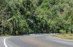 Route avec le panneau d'avertissement glissant de trottoir photos stock