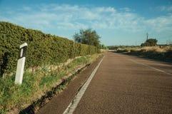 Route avec le poteau d'avertissement réfléchi à côté des arbustes photographie stock