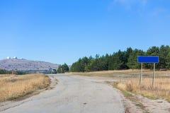 Route avec le poteau de signe et ciel bleu avec des nuages Photographie stock libre de droits