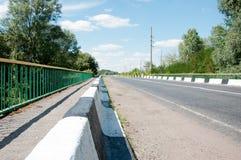 Route, barrière, inscription, arbres et ciel bleu Photographie stock libre de droits