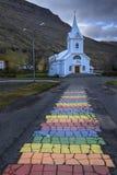 Route bleue d'église et d'arc-en-ciel dans Seydisfjordur Image stock