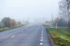 Route brumeuse avec des enjeux de neige photographie stock