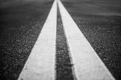 Route d'asphalte avec les lignes blanches de marquage routier Images libres de droits