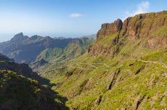 Route d'enroulement menant à un petit village entre les montagnes photos stock