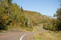 Route d'enroulement par la forêt d'automne Photographie stock