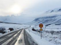 Route d'hiver avec la montagne du côté de la route couverte de s image libre de droits