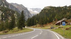 Route dans les Alpes se transformant à gauche en vallée et tunnel de pin Photographie stock libre de droits