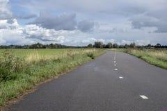 Route de bicyclette, avec des lignes de route, sous un ciel nuageux images libres de droits