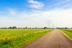 Route de campagne apparemment sans fin dans une zone rurale avec des pylônes de puissance Image stock