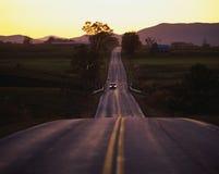 Route de campagne au coucher du soleil avec venir de véhicule photo libre de droits